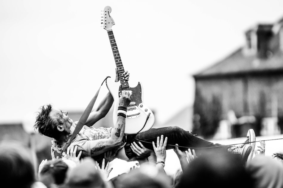 Guitarist crowdsurfing on his back