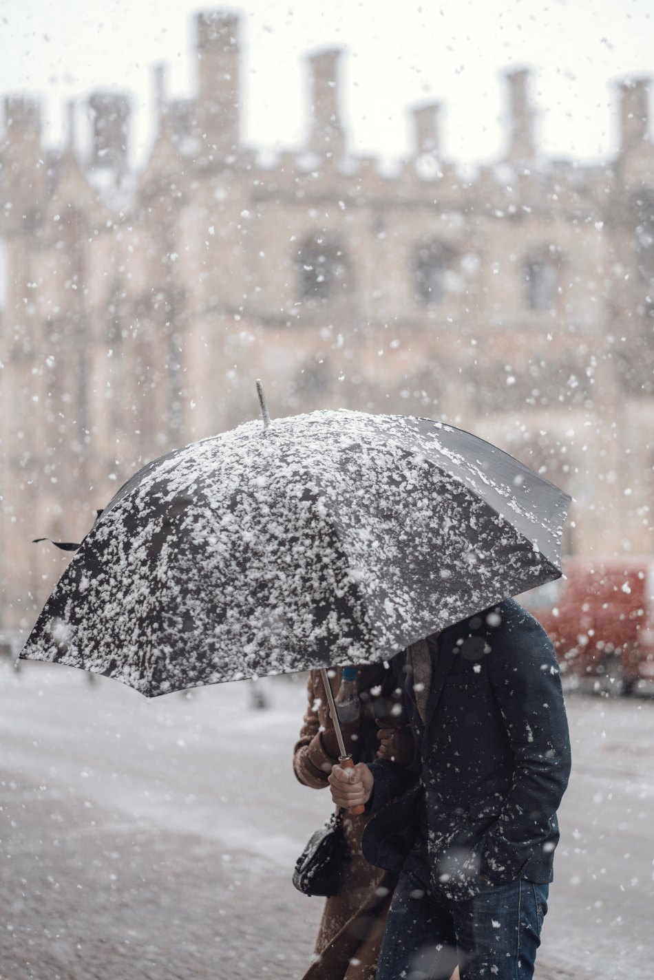 London man and woman holding umbrella while it's snowing
