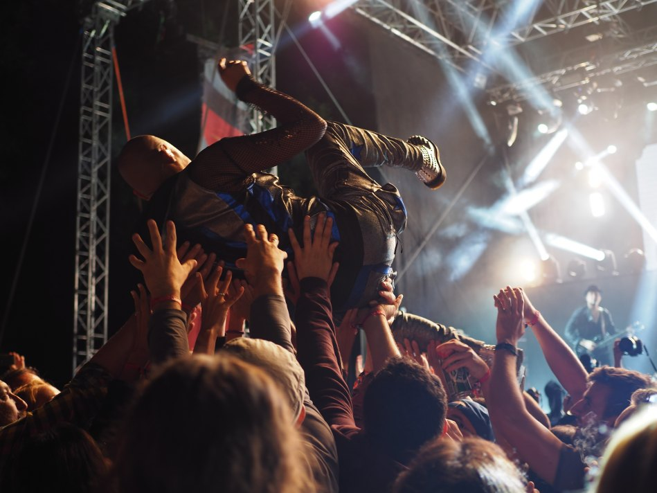 Rock singer crowdsurfing on his back