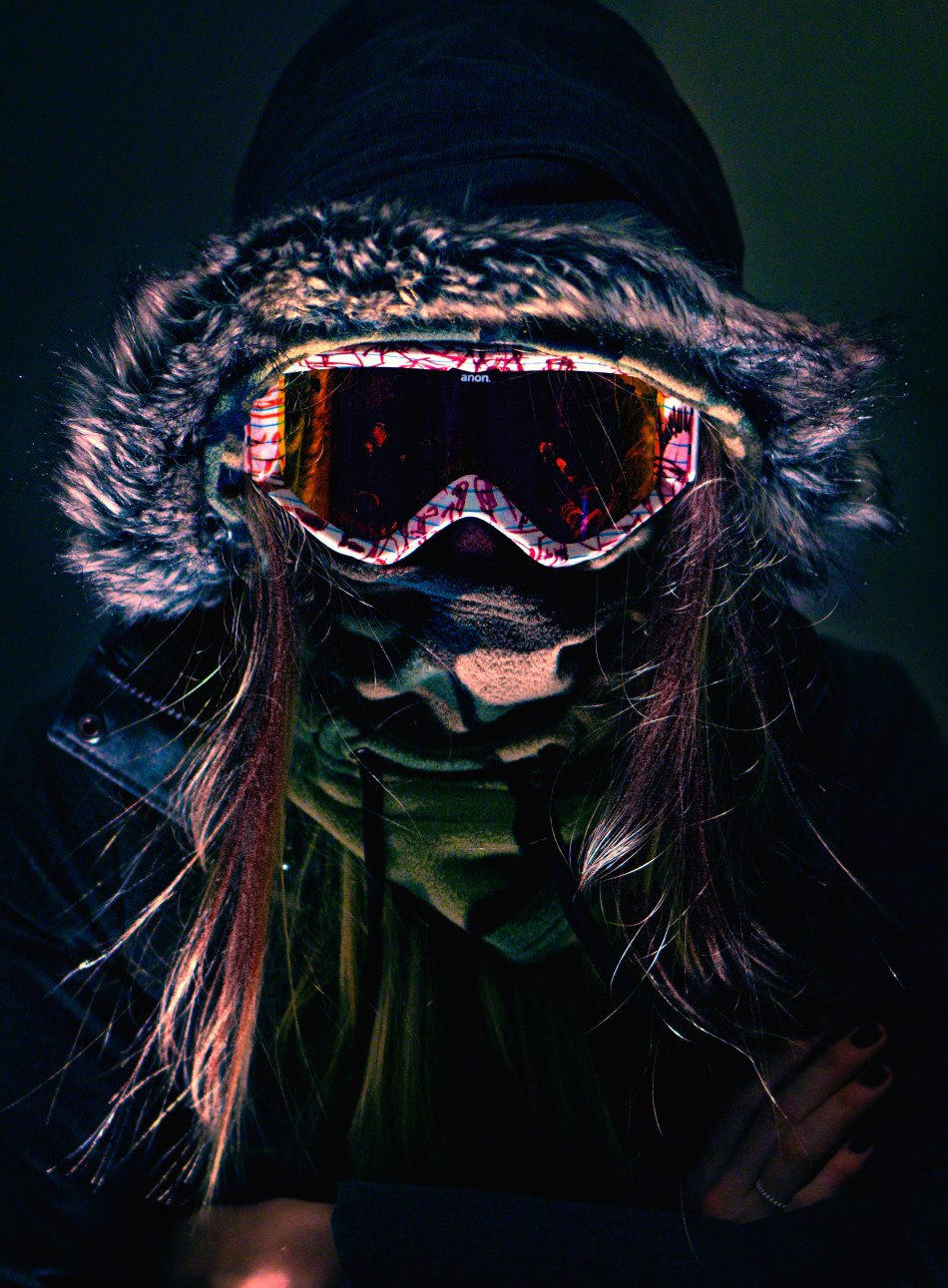 Woman standing in the dark with covered face, wearing scarf, hooded jacket and ski goggles