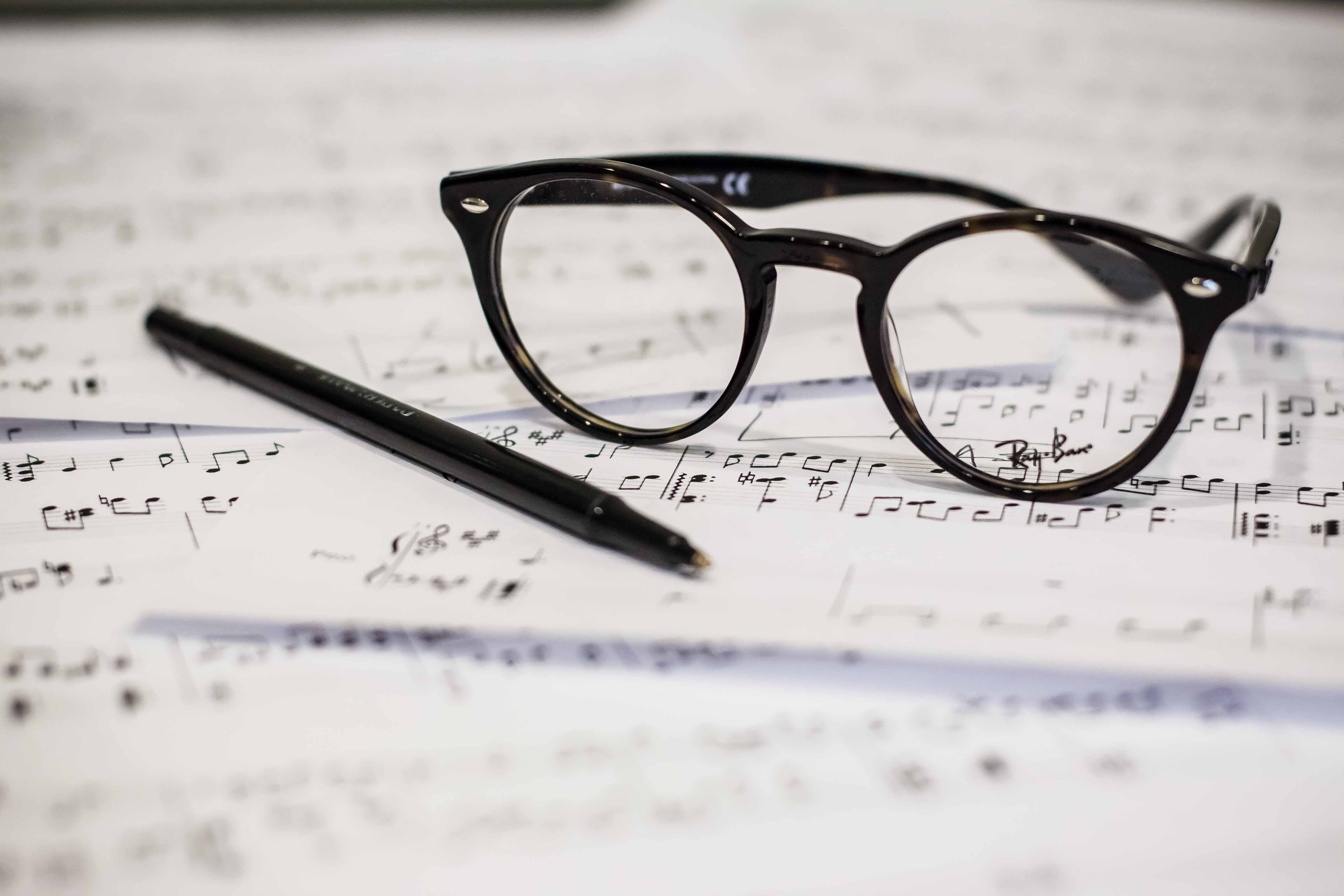 Black reading glasses and pen resting on sheet music