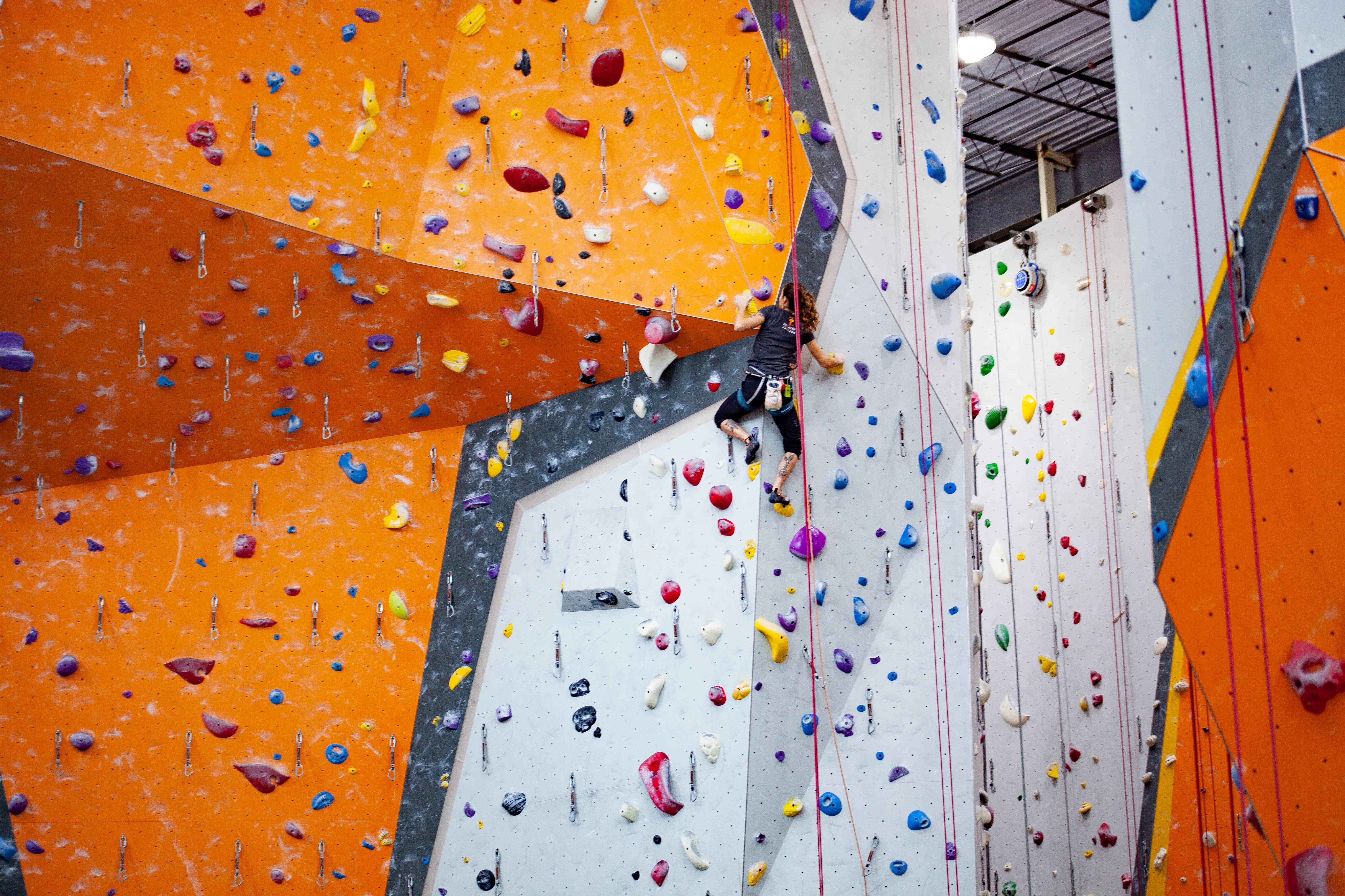 Person climbing up indoor climbing wall