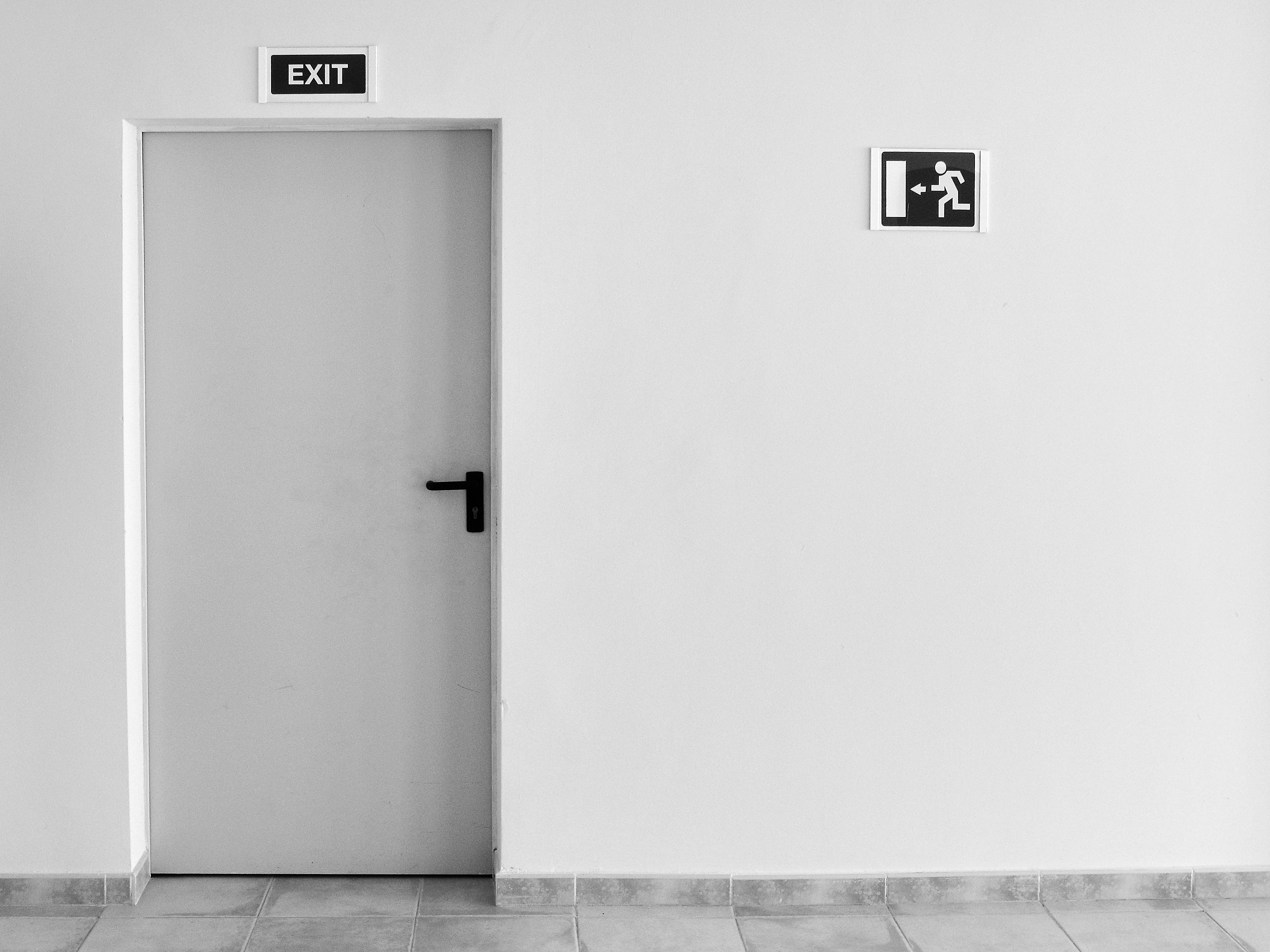 Black and white photo of an emergency exit sign and door